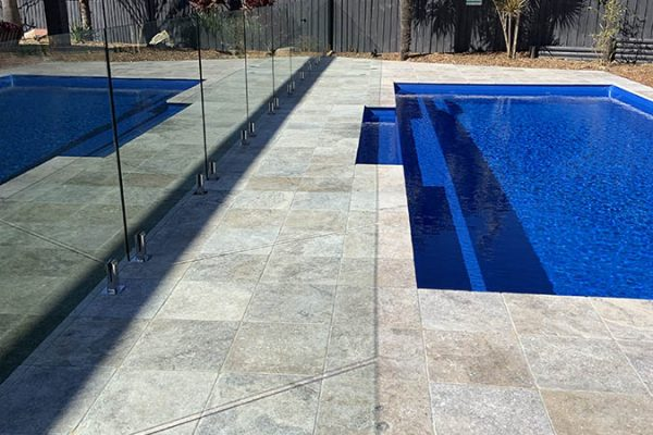 glass pool fencing enclosing deep blue pool in central coast