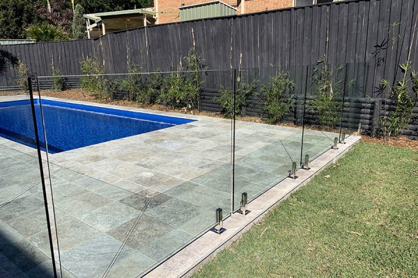 glass pool fencing separating green grass and blue pool in central coast