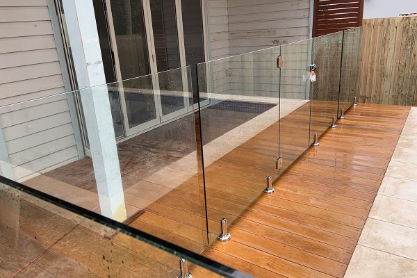 glass pool fencing and wooden outdoor floorboards