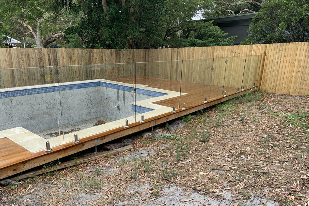 glass pool fencing with empty pool and backyard central coast